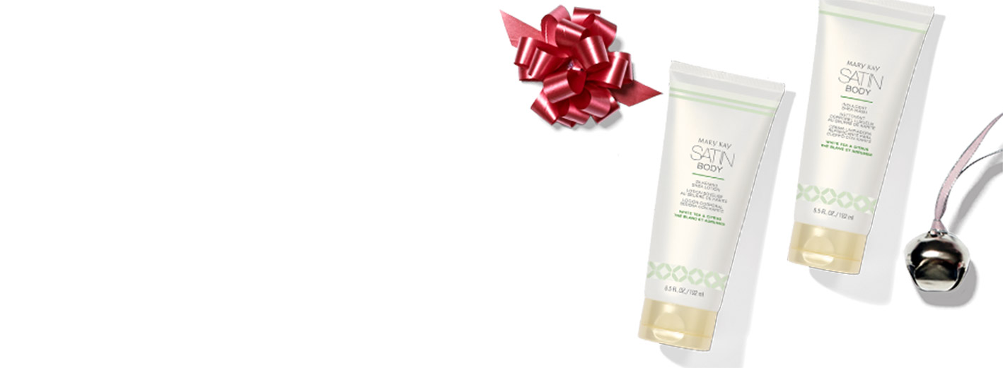 Satin Body Indulgent Shea Wash and Silkening Shea Lotion styled with a gift bow and bell on a white background.
