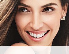 A smiling woman is wearing a Mary Kay makeup artist look that incorporates a hint of color and metallic neutrals to make skin appear sun-kissed for summer.